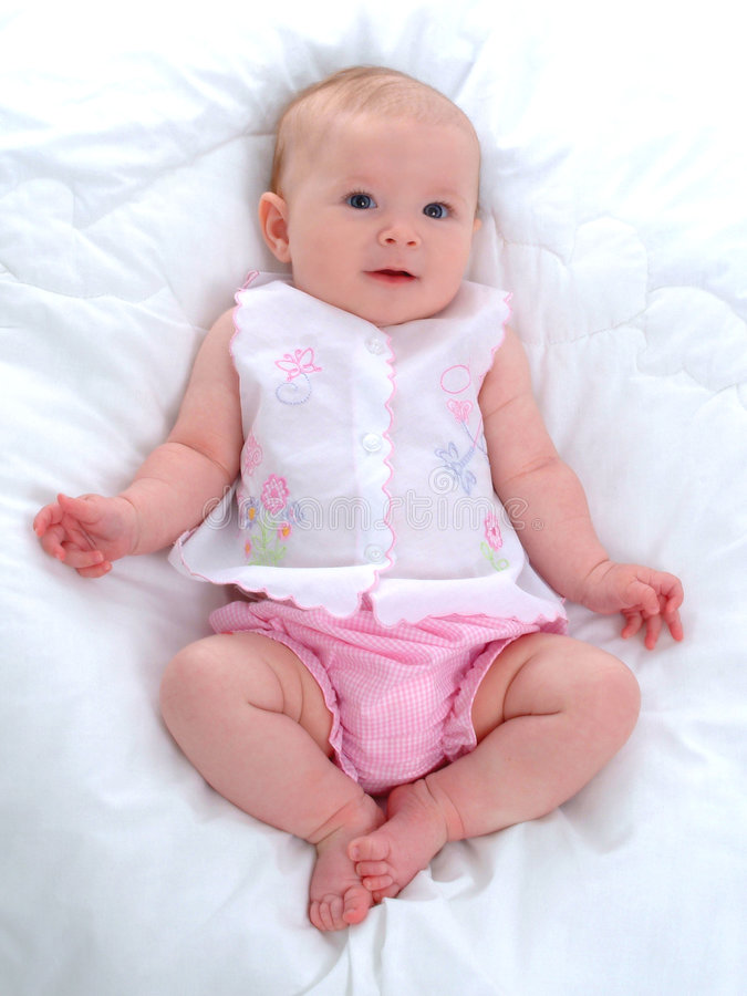 Baby Girl. Sitting in front of white background on blanket stock photo