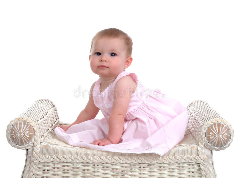 Baby Girl. Sitting on wicker bench royalty free stock photography