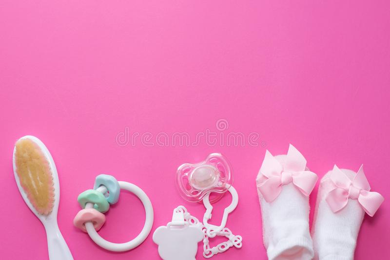 Baby girl accessories soother, wooden toy, socks and teether on pink background with copy space. Top view, flat lay.  royalty free stock photo