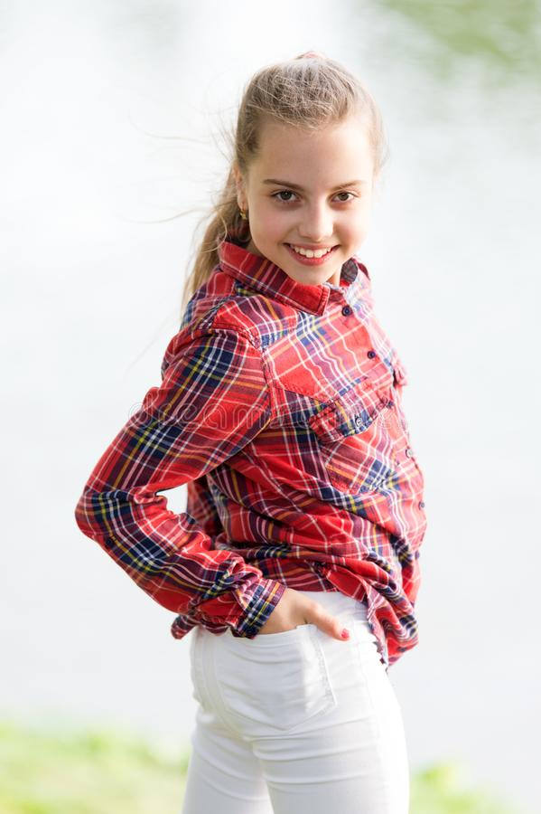 A baby girl. Adorable baby with long blond hair smiling in casual plaid style outdoor. Happy little baby wearing fashion. Summer outfit. Small baby with cute stock photography