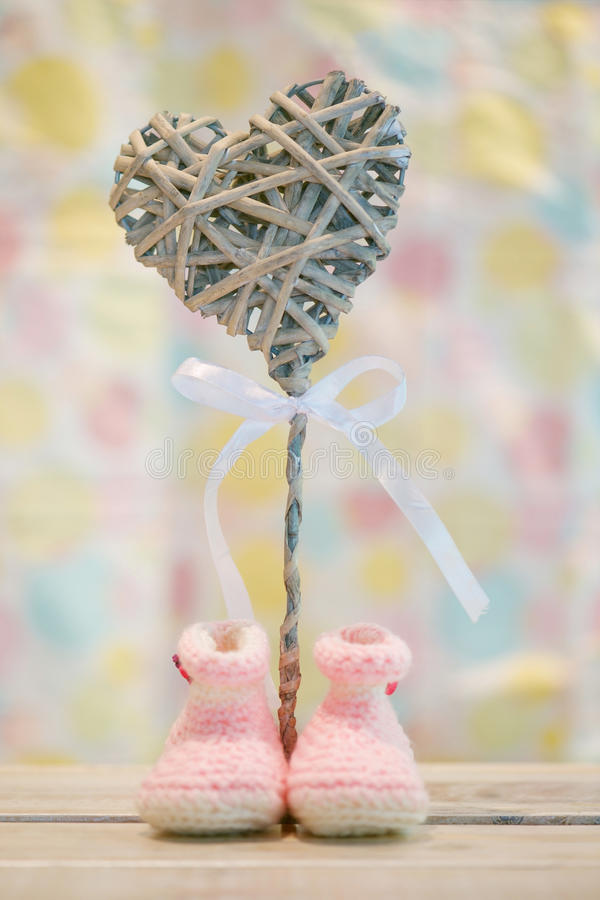 Baby girl announcement. Cute handmade pink baby girl crochet booties and wooden heart on pastel background - concept for baby girl birth announcement royalty free stock images