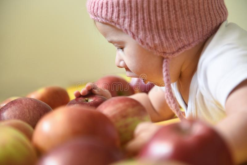 Baby girl and apples stock image