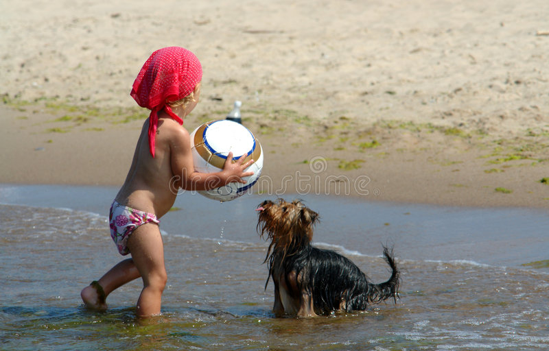 A baby girl with a ball and he stock image