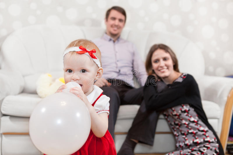 Baby girl with balloon and father and mother in domestic room. Caucasian baby girl with balloon and father and mother in domestic room stock image