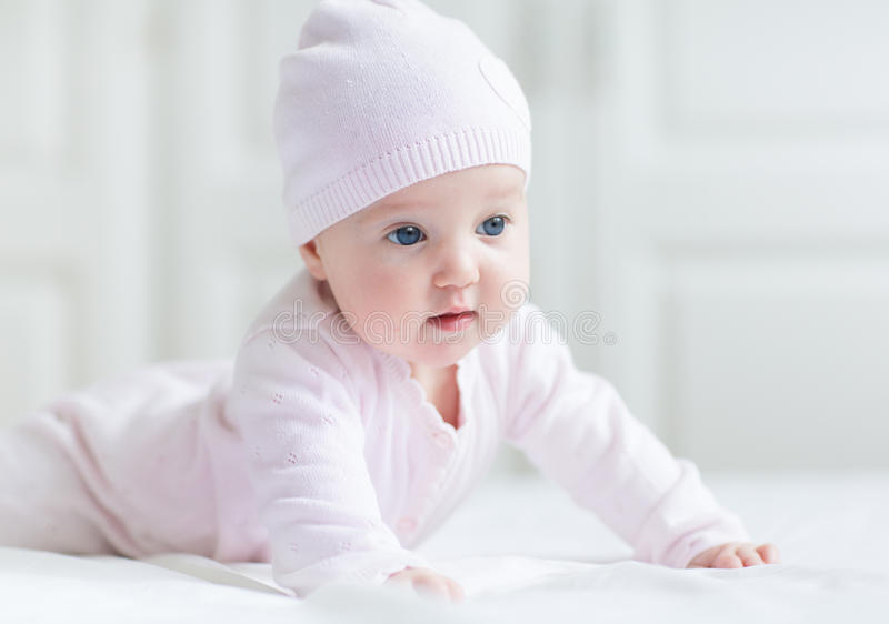 Baby girl with big blue eyes on white blanket. Beautiful baby girl with big blue eyes on a white blanket royalty free stock photos