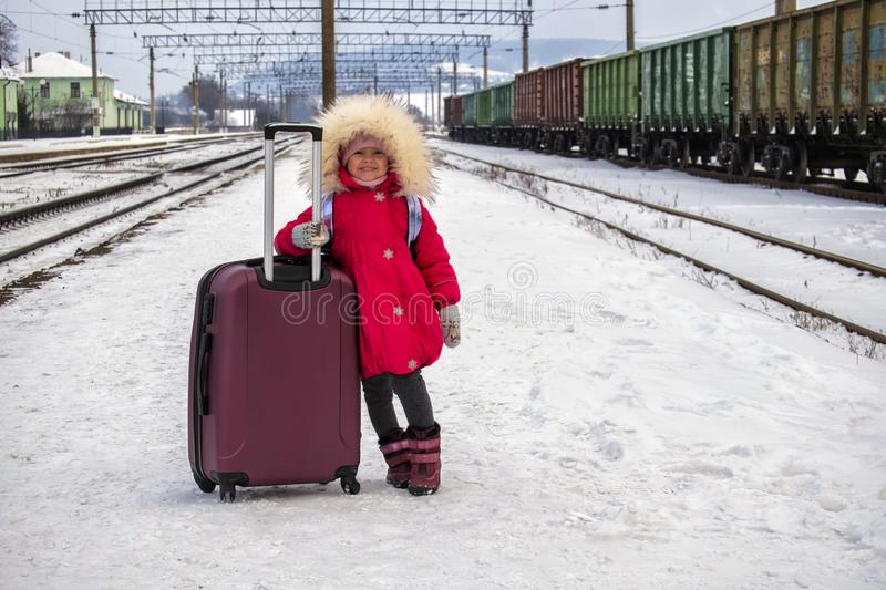 Baby girl with a big suitcase is standing on the empty snow-covered platform of the railway station. Baby with a big suitcase is standing on the empty snow royalty free stock image