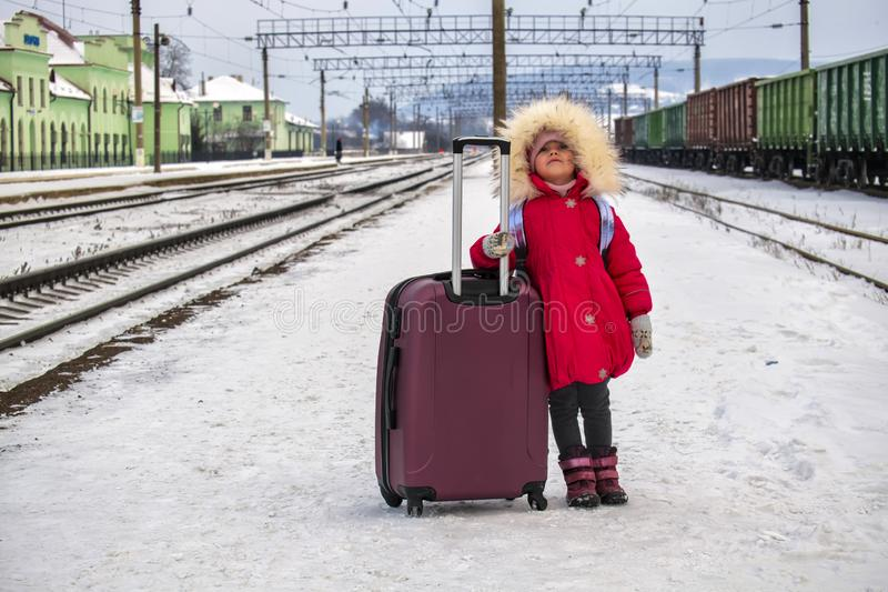 Baby girl with a big suitcase is standing on the empty snow-covered platform of the railway station and looks to the sky royalty free stock photo