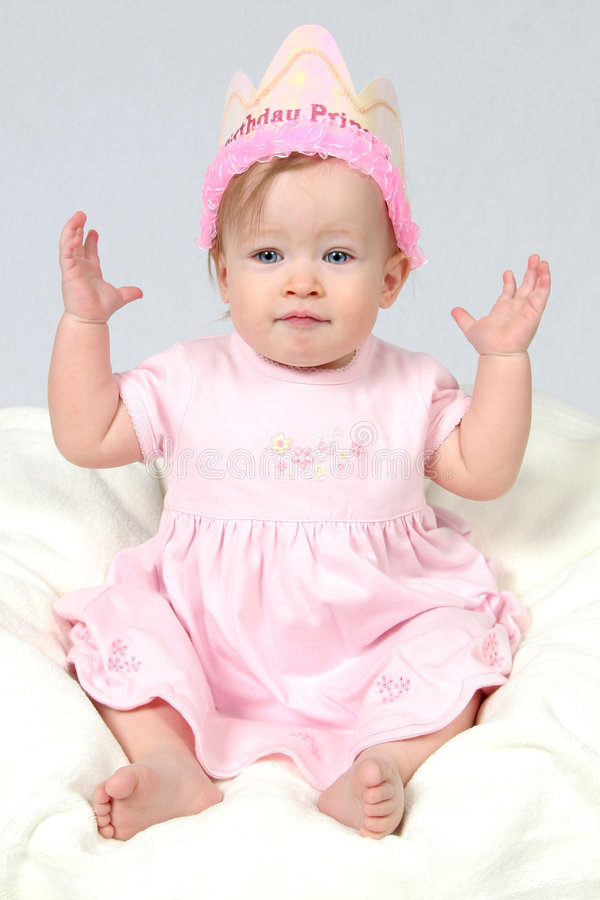 Baby Girl With Birthday Hat an. Little Baby Girl in Pink dress and birthday hat and hands in air stock photo