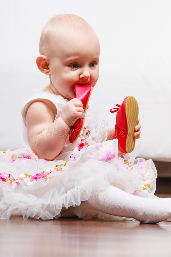 Baby girl biting shoe. Infant in time of teething. Sweet cute baby girl biting chewing red shoe. Young adorable child wearing white princess dress stock photography