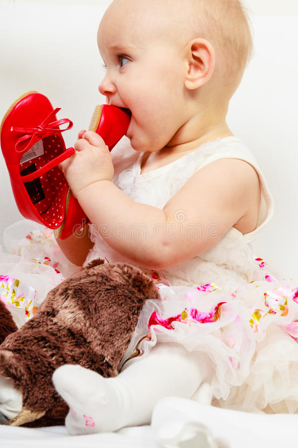 Baby girl biting shoe. Infant in time of teething. Sweet cute baby girl biting chewing red shoe. Young adorable child wearing white princess dress royalty free stock photo
