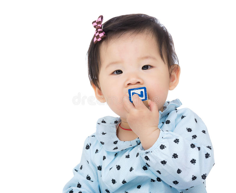 Baby girl biting toy block. Isolated on white stock images