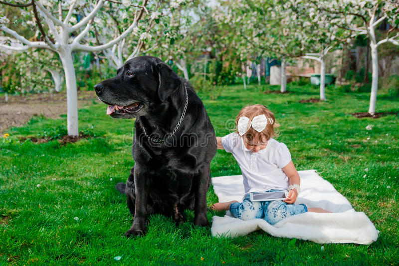 Baby girl with black labrador royalty free stock photography