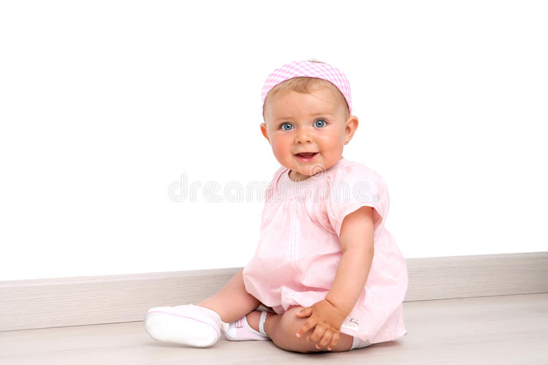 Baby girl with blue eyes sitting on the floor. Friendly blue eyed baby girl wearing pink dress and pink head band sitting on the floor indoors stock image