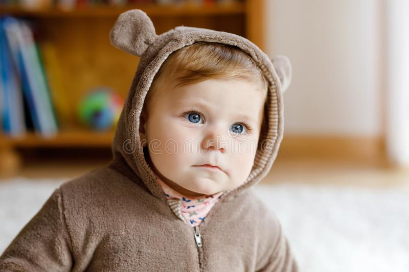 Baby girl with blue eyes wearing brown bear winter overal in sunny bedroom. Newborn child being dressed for an outdoor. Walk. Nursery for children. Textile and stock photo