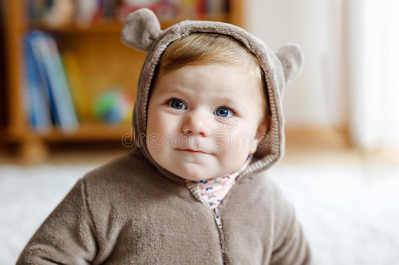 Baby girl with blue eyes wearing brown bear winter overal in sunny bedroom. Newborn child being dressed for an outdoor. Walk. Nursery for children. Textile and royalty free stock photos