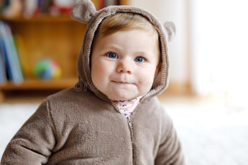 Baby girl with blue eyes wearing brown bear winter overal in sunny bedroom. Newborn child being dressed for an outdoor. Walk. Nursery for children. Textile and royalty free stock photo