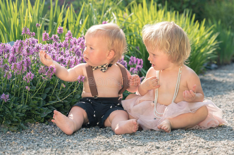 Download baby girl and boy sitting in a beautiful garden looking at flowers stock photo