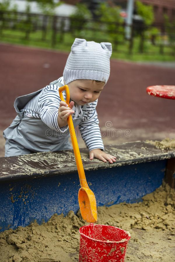 Baby girl boy 1 year old in a hat playing in the sandbox with a shovel and bucket stock photos