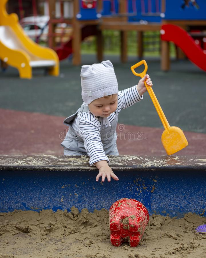 Baby girl boy 1 year old in waterproof pants on the straps playing in the sandbox with toys. Little baby on a walk stock photo