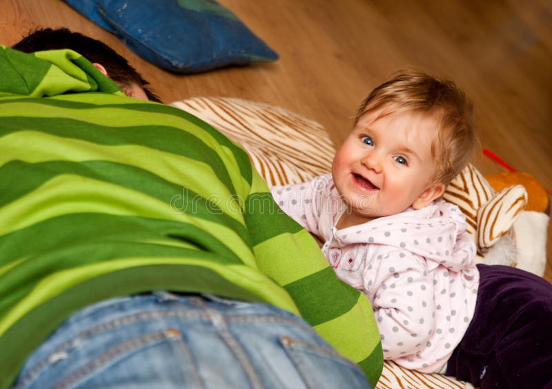 Baby girl and brother on floor. Smiling baby girl and her older brother lying on the floor together stock photos