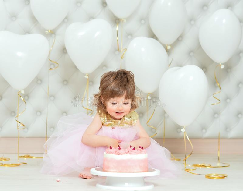 Portrait of baby girl with cake on her birthday. Baby girl with cake on her birthday posing at home royalty free stock image