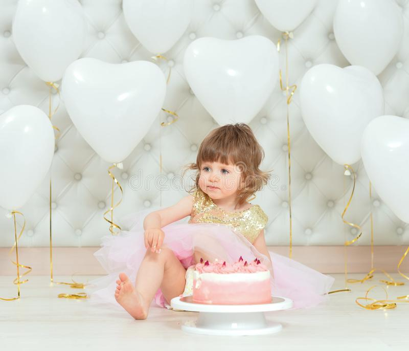 Portrait of baby girl with cake on her birthday. Baby girl with cake on her birthday posing at home stock photo