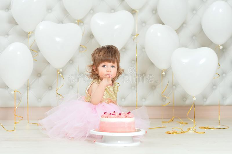 Portrait of baby girl with cake on her birthday. Baby girl with cake on her birthday posing at home stock images