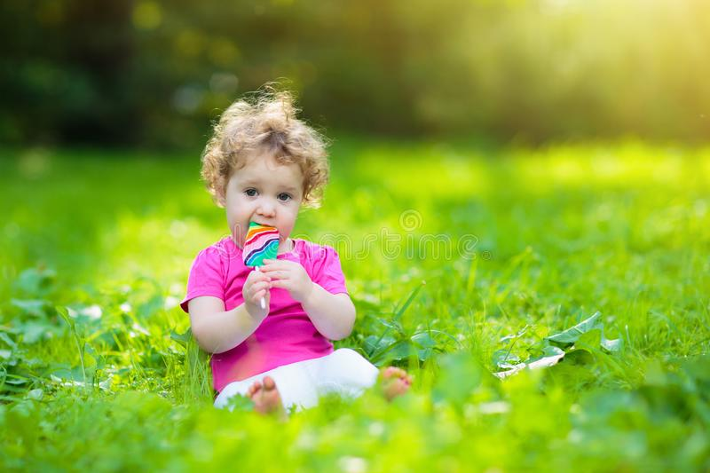Baby girl with candy. Child with lollipop stock photography
