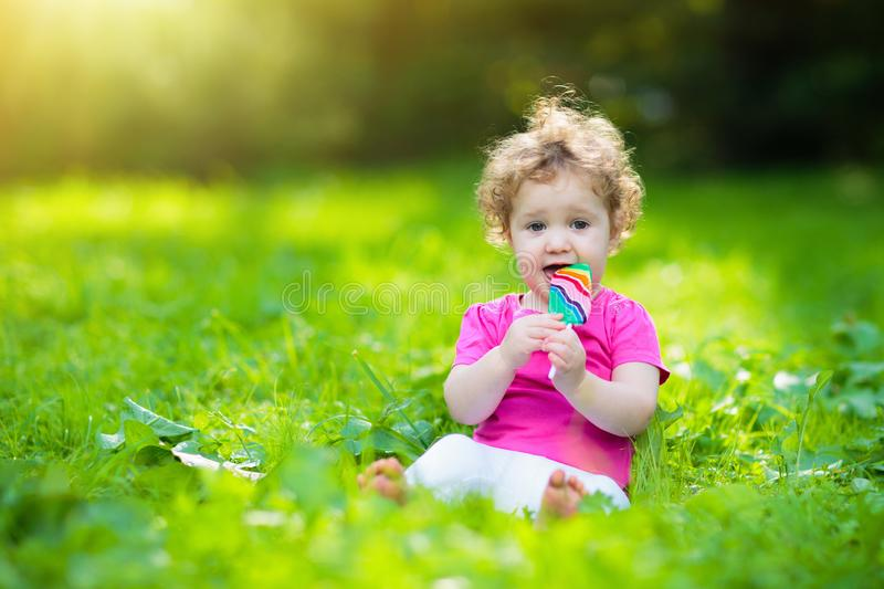 Baby girl with candy. Child with lollipop stock image