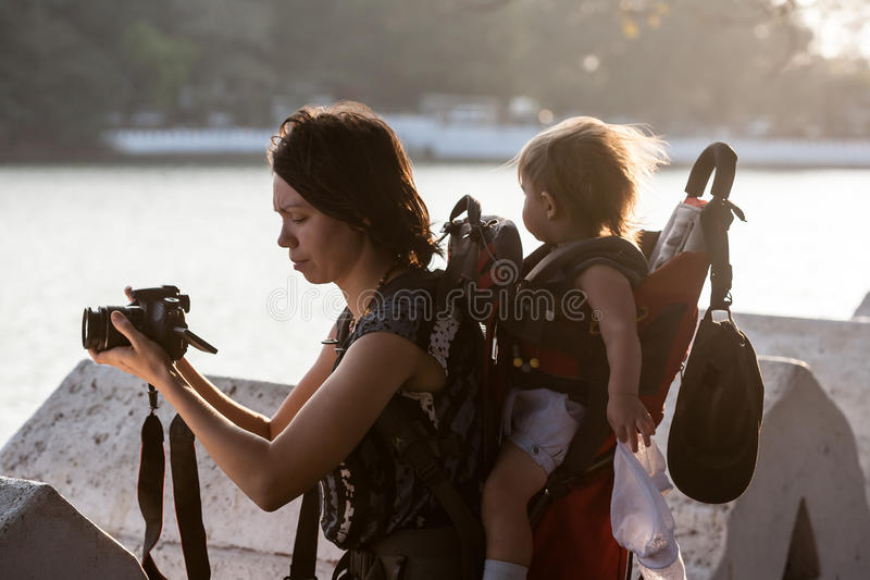 Baby girl in carrying backpack enjoying travel adventure, royalty free stock images