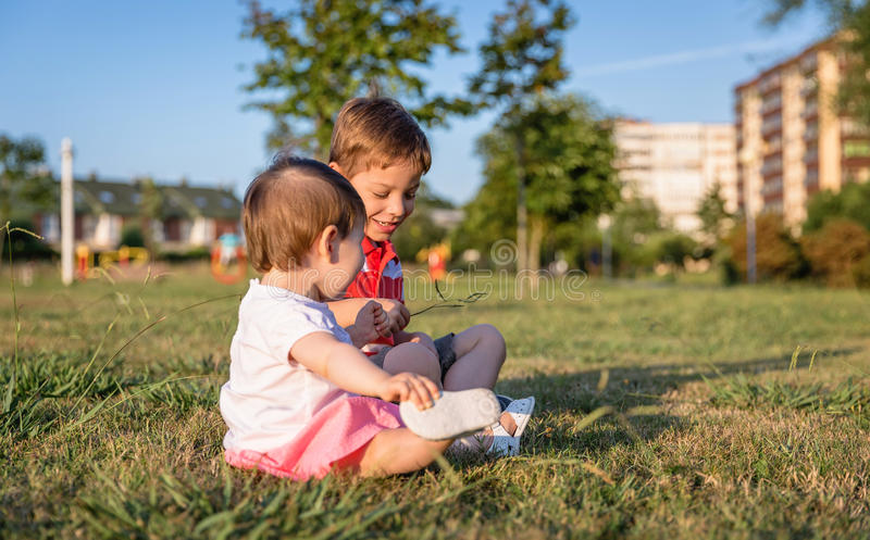 Baby girl and child playing sitting on a grass. Adorable baby girl and cute boy playing sitting on the grass park in a sunny summer day royalty free stock images