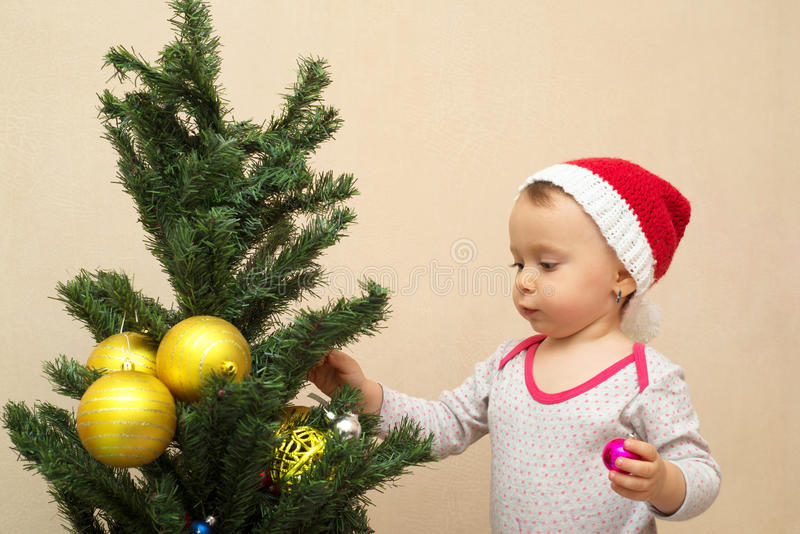 Baby girl with Christmas ball stock image
