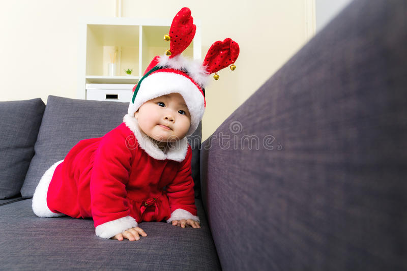 Baby girl with christmas dressing and creeping on sofa stock images