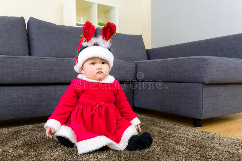 Baby girl with christmas dressing and seating on carpet stock photo