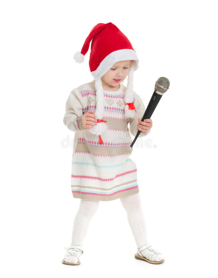 Baby girl in Christmas hat dancing with microphone stock photos