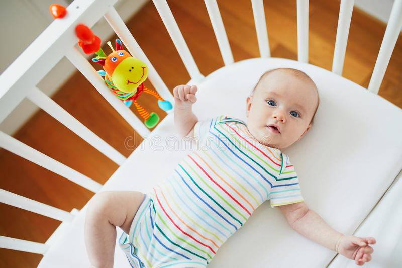 Baby girl in co-sleeper crib. Adorable baby girl in co-sleeper crib attached to parents ` bed. Little child having a day nap in cot. Infant kid in sunny nursery stock photography