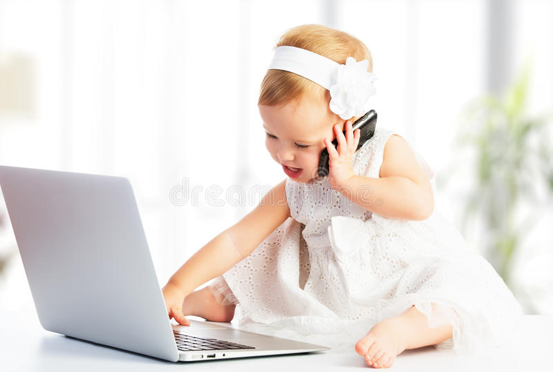 Baby girl with computer laptop, mobile phone royalty free stock images