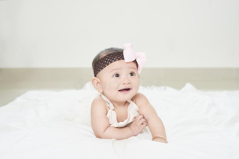 A baby girl is crawling along the floor with an inquisitive look on her face. Horizontal shot stock images
