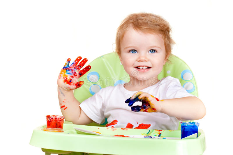 Baby girl creates picture with painted hands stock images