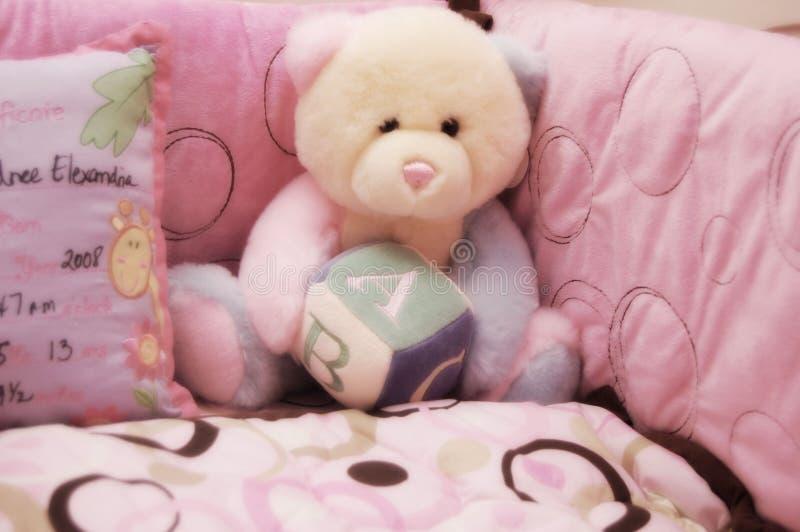 Baby girl crib and teddy bear stock images