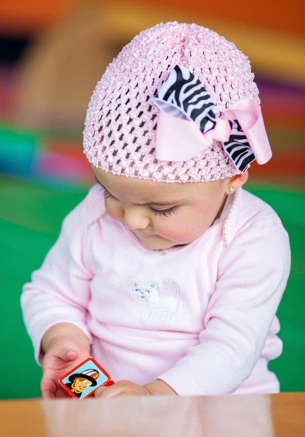 Baby girl with a cube stock photos
