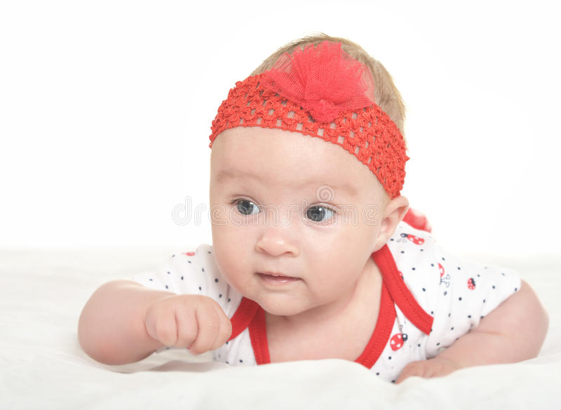 Baby girl in cute clothes. Adorable baby girl in cute clothes on blanket royalty free stock photography