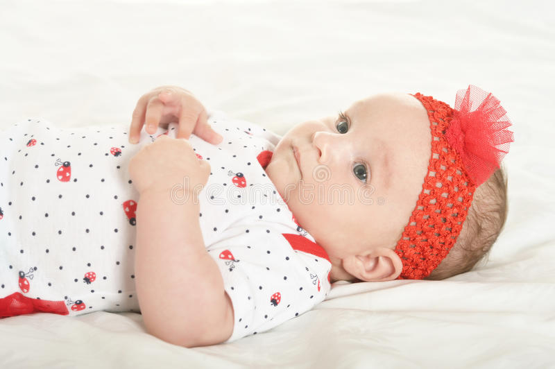 Baby girl in cute clothes. Adorable baby girl in cute clothes on blanket royalty free stock image