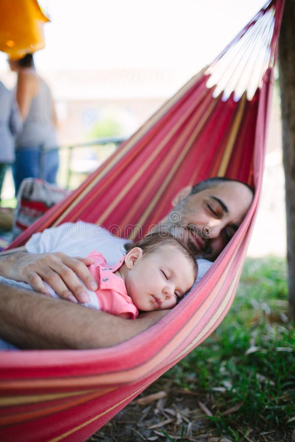Father and baby daughter sleeping on a hammock royalty free stock photo