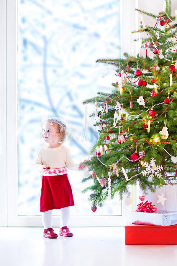 Baby girl decorating christmas tree stock photo image for Baby christmas tree decoration