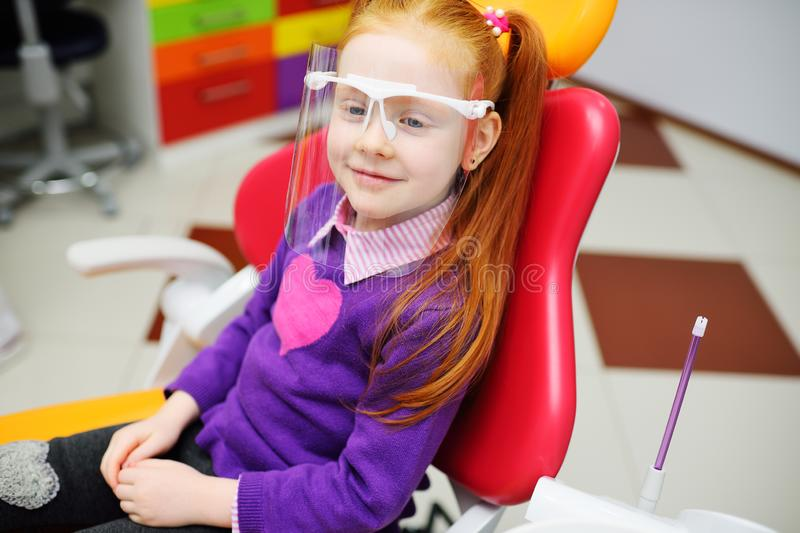 Baby girl in dental glasses smiling sitting in dental chair. royalty free stock photos