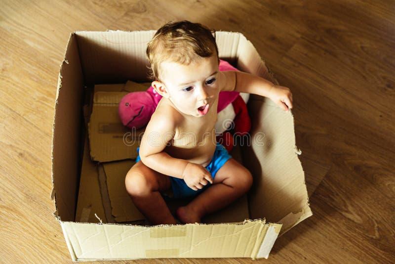 Baby girl die in een kartonnen doos speelt met haar verbeelding stock afbeeldingen