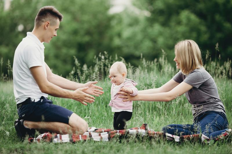 Baby girl doing first steps. Happy parents supporting their daughter learning to walk. Family playing and enjoying time together. Childhood, parenthood, child stock image