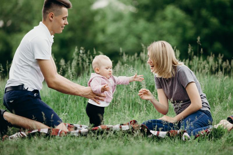 Baby girl doing first steps. Reaching hands to mother. Happy parents supporting their daughter learning to walk. Family playing enjoying time together royalty free stock images