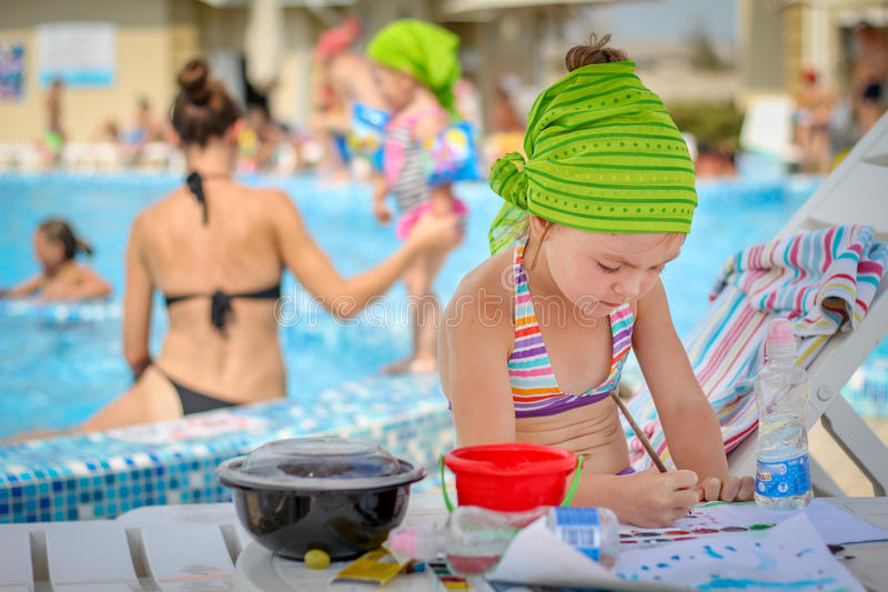 Download Baby Girl Drawing Near The Pool Stock Image